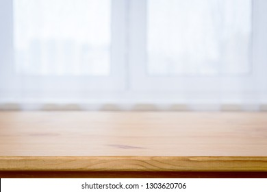 Wooden table surface on blurred white window background