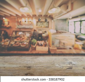 wooden table top with blur of coffee shop interior background