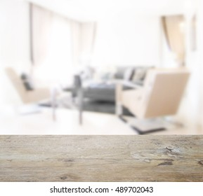 wooden table top with blur of modern living room interior in brown color decoration