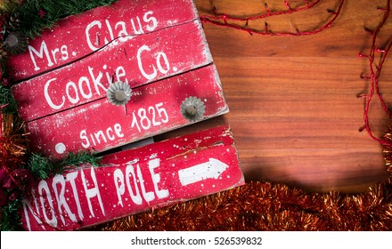 Wooden table top Christmas sign pointing to the North Pole, home of Mrs. Santa Claus. Red and white goes beautifully with table top structure, add your product or message on top.