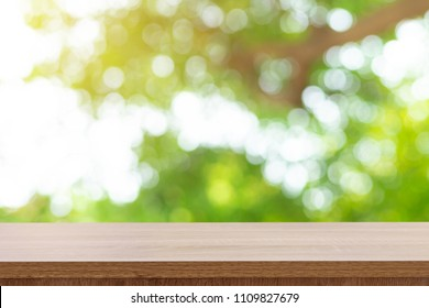 Wooden table top and green bokeh display montage for product with space.
