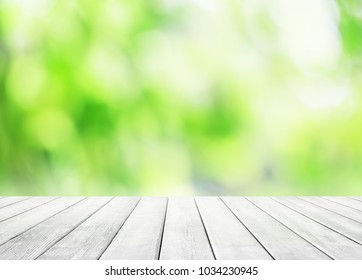Wooden table top on blur abstract green background. Spring green abstract background with bokeh light.