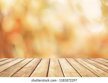 Wooden table top on blur abstract autumn background. Autumn golden abstract background with bokeh light.