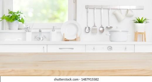 hölzerner Tisch auf unscharfem Küchenraum und Fensterhintergrund