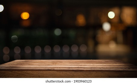Wooden table top on blurred shop window of cafe with light bulb. Background for product display montage or key visual design.