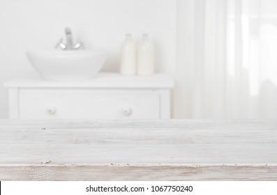 Wooden table top over blurred bathroom furniture with copy space