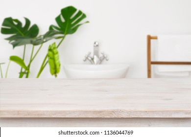 Wooden table top for product display over blurred bathroom interior