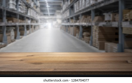 Wooden table top for product display montage. Blured shelves with goods in store at factory warehouse storage in the background. Stock concept.