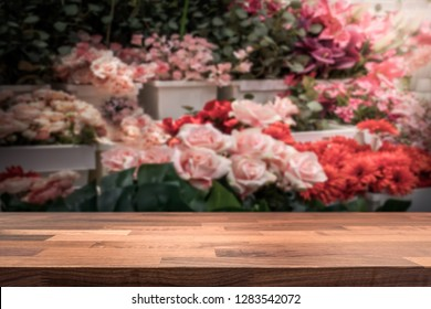 Wooden table top / shop counter in front of blurred flower store. Background for product display montage. Copy space design.