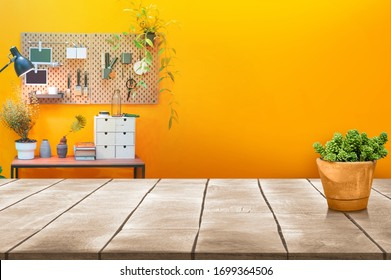 Wooden table top and tree pot with paintbrush tool on board hanging on the yellow wall