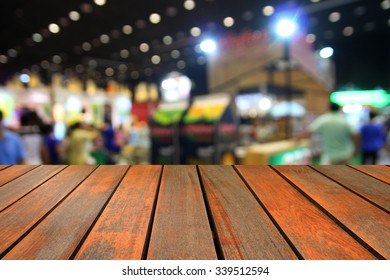 Wooden table and trade show area. Blurred background