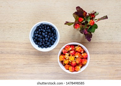 wooden table with two white ceramic bowls with cloudberries and blueberries, vase with a bouquet of cloudberries, top view