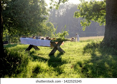 wooden table under oaks with traditional Latvian food. Old Latvian culture tradition LIGO. Midsummer night celebrating in Latvia.