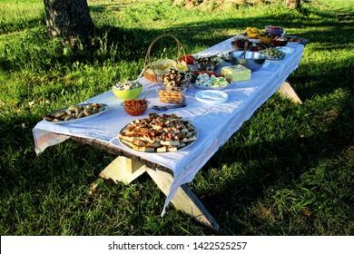 wooden table under oaks with traditional Latvian food. Old Latvian culture tradition LIGO. Midsummer night celebrating in Latvia.