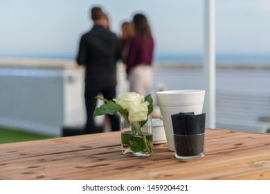 A wooden table with a vase with a white rose. The background consist of a blurred group of attendees on terrace below a blue sky.