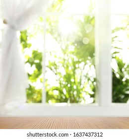 Wooden table and view through window on garden. Springtime