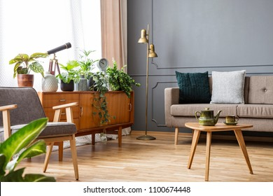Wooden table in vintage living room interior with cabinet between sofa and armchair. Real photo