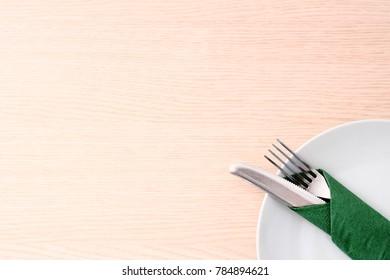 Wooden table with white dish and cutlery background.