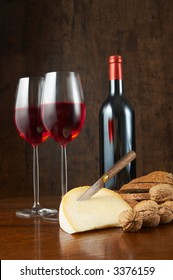 Wooden table with wine, nuts, cheese and bread