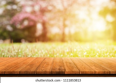 Wooden table or wood floor isolated on blurred colorful nature background. For your product placement or montage with focus to the table top in the foreground. Empty wooden brown shelf. shelves