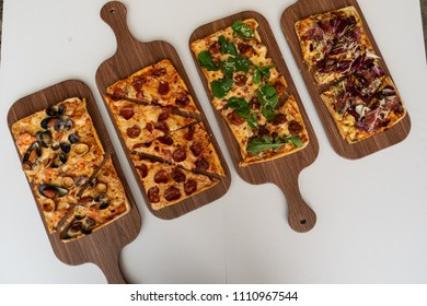 Wooden tables with rectangular Pizza Overhead view of various flavors