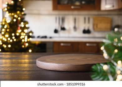 Wooden tabletop with cutting board and blurred kitchen with Christmas tree. Background for display or montage your products.