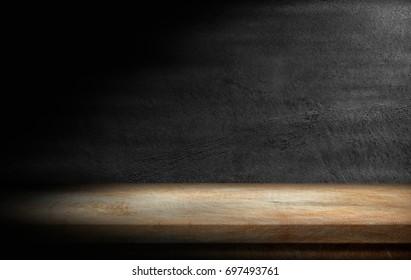 Wooden tabletop in dark room background.