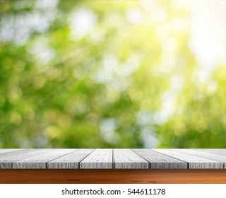 Wooden tabletop with fresh green nature blurred background use for products display.
