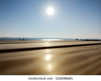 Wooden tabletop perspective view over Danish sea during summer captured in a sunny day. The picture was taken in Horsens, Denmark at shore.