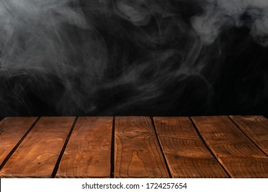 Wooden tabletop with smoke on the background
