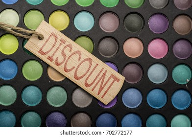 Wooden tag placed on colorful makeup palettes writing discount