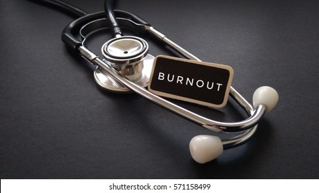 Wooden tag written with BURNOUT and stethoscope on black background. Medical and Healthcare Concept