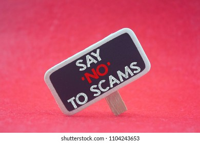 wooden tag written say 'no' to scams over red background
