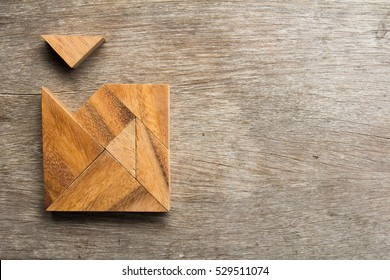 Wooden tangram with one piece is wait to fulfill the square shape on wood background