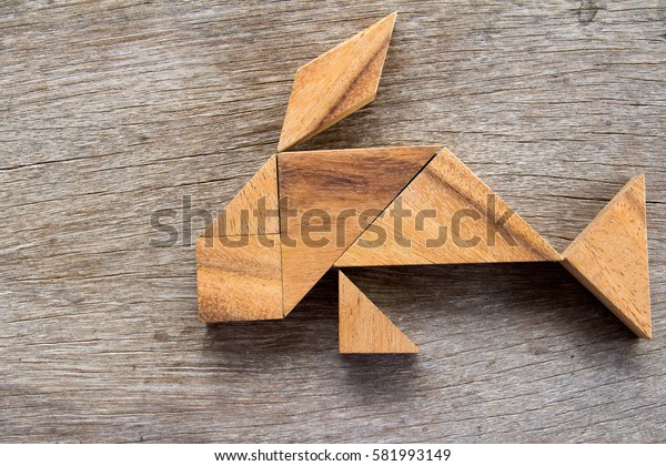 Wooden tangram puzzle in fish shape background