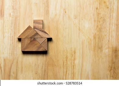 Wooden tangram puzzle in home shape for dream home or happy life concept
