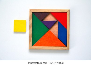 wooden tangram set in a box, misplaced. one piece is misfit, out of box, near the set.
