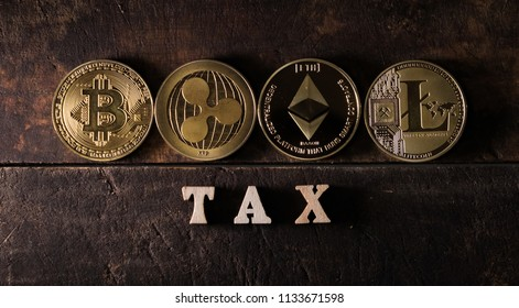 Wooden TAX word with popular cryptocurrencies on dark wood background
