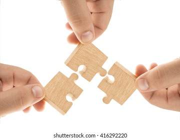 Wooden Teamwork - group of people holding wood puzzle pieces. three hands. Isolated on white background