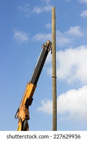 Wooden telephone pole hangs vertically in the air from a yellow crane. Crane hook lifting the wooden telephone pole out.