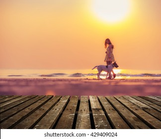 Wooden terrace with beautiful girl and her dog during sunset background
