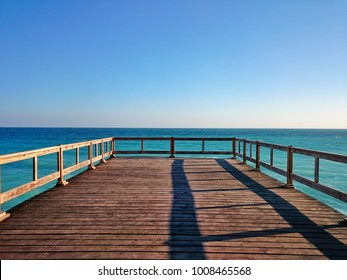Wooden terrace dock or pier deck. Wooden dock (pier) on blue sea beach & sky background. Perspective view of wooden river pier deck, seashore dock or deck with clear sky and turquoise sea water.