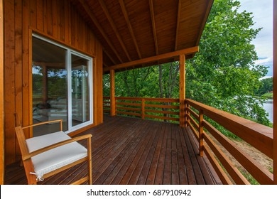 Wooden terrace of wooden house. Yellow wooden planking. Panorama windows. Outside furniture. Perfect view on oak forest.