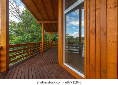 Wooden Terrace Of Wooden House. Yellow Wooden Planking. Panorama Windows.  Outside Furniture.