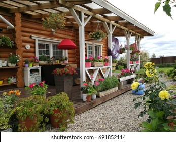 A wooden terrace and on it an abundance of flowers in pots