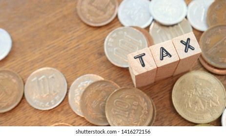 Wooden Text Block of Tax and Pile of Coins