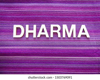 "Wooden text letters with the Sanskrit word ""DHARMA"" for a sign, banner, placard or wallpaper on a vibrant purple woven texture background"