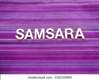 "Wooden text letters with the Sanskrit word ""SAMSARA"" for a sign, banner, placard or wallpaper on a vibrant purple woven texture background"