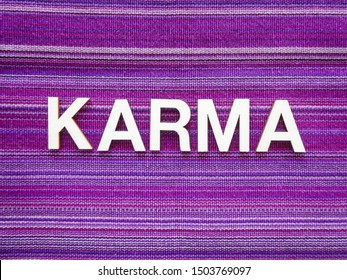 "Wooden text letters with the Sanskrit word ""KARMA"" for a sign, banner, placard or wallpaper on a vibrant purple woven texture background"