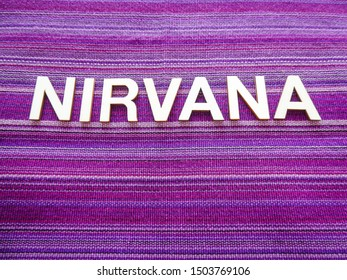 "Wooden text letters with the Sanskrit word ""NIRVANA"" for a sign, banner, placard or wallpaper on a vibrant purple woven texture background"